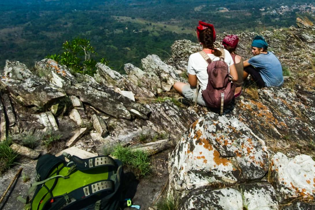 Three backpackers sit on a mountain top in Ghana